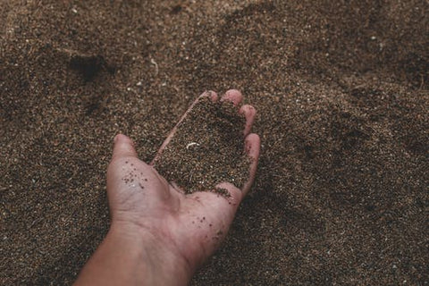 A man holds a handful of soil.
