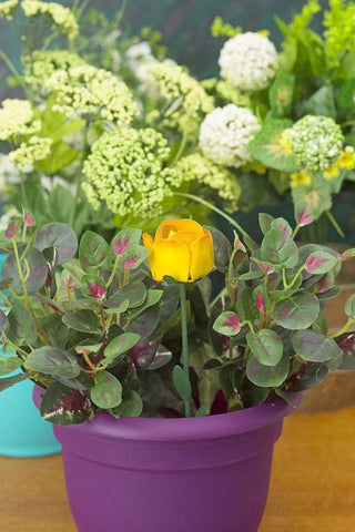 A yellow rose plant pick is staked into a potted plant.