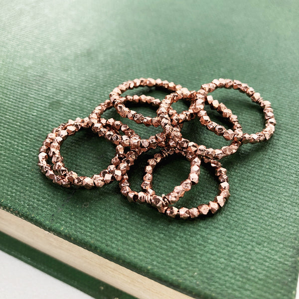 Stacks of faceted rose gold rings on a green book
