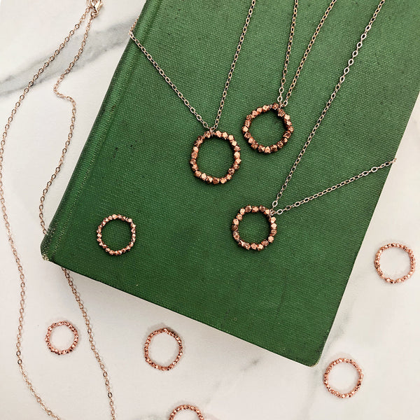 rose gold rings and necklaces on a green book