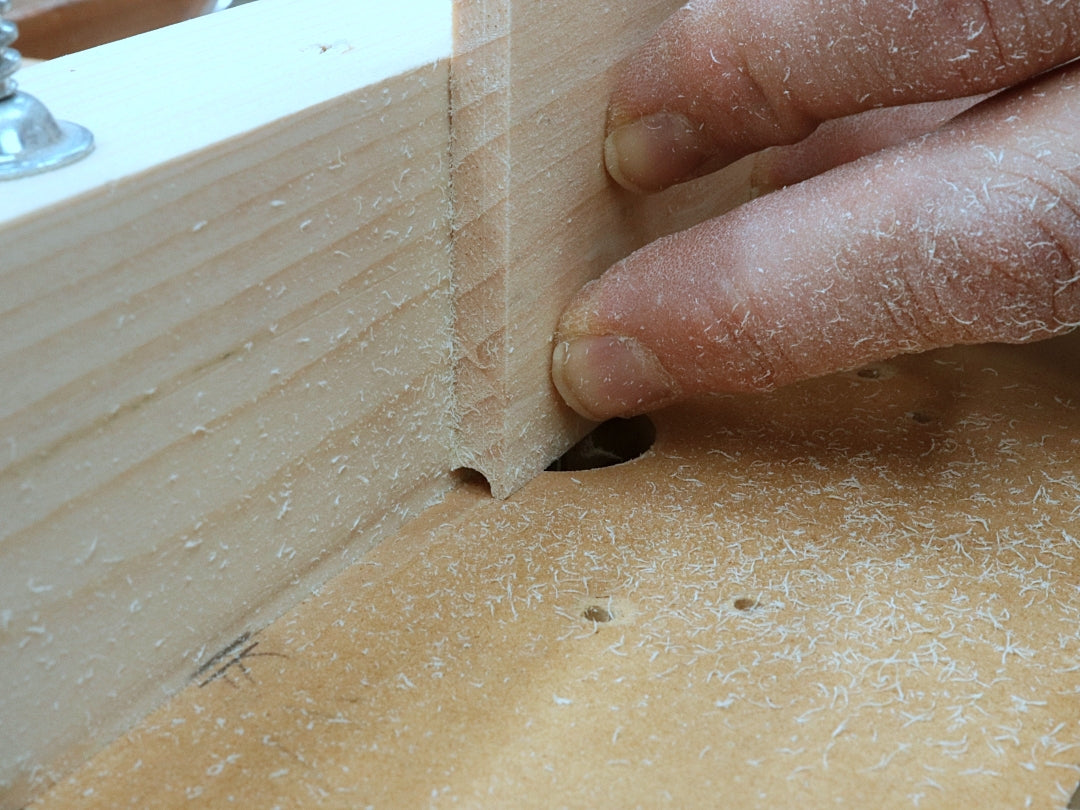 Rob Cosman using a whiteside router bit and his router table to cut a groove in a box side to accept the dowel for his woodhinge
