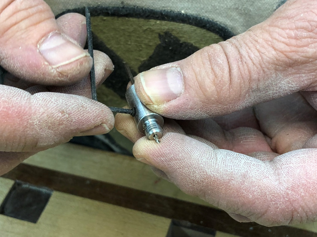 Tightening the set screw that locks in the drill bit in the wood-hinge drill jig