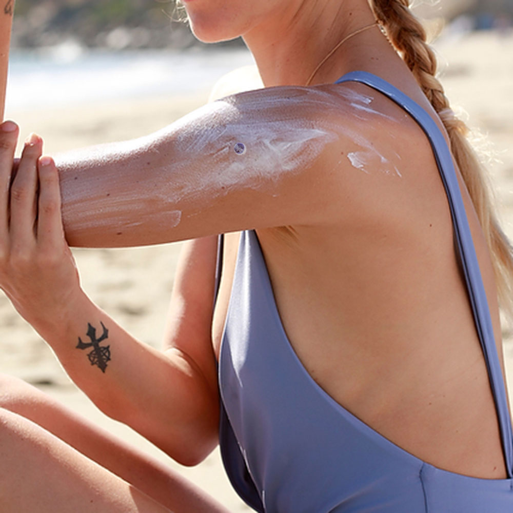 SPOT on woman's arm. Woman is applying sunscreen over SPOT.