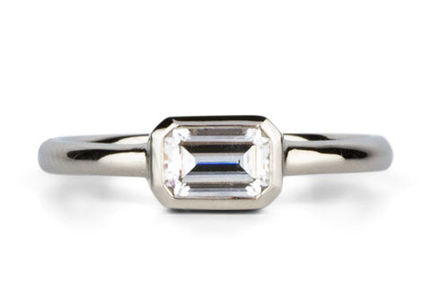 Bezel Set ring with an emerald cut moissanite in white gold