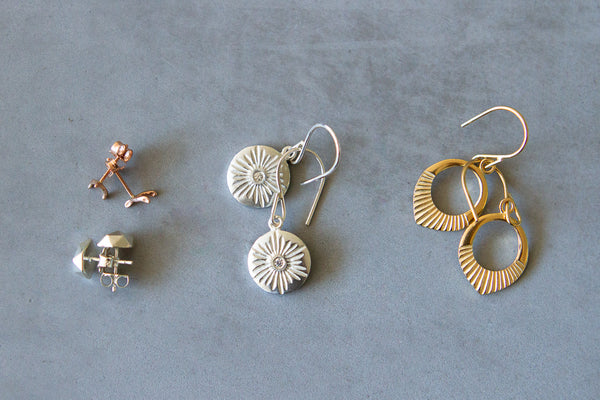 Store earring mates together. Four pair of earrings laying down with each pair hooked together