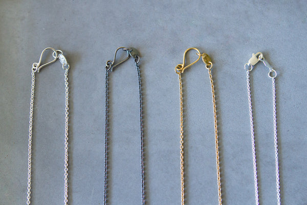 Close the clasp on your necklaces to avoid tangles. Four necklaces with hooked clasps in a row.