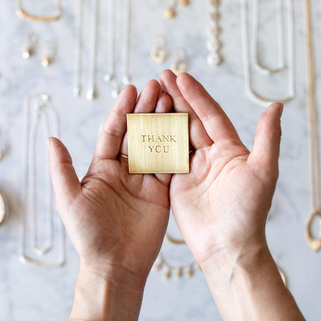 """Brass tile engraved with the words """"thank you"""" in a pair of hands"""