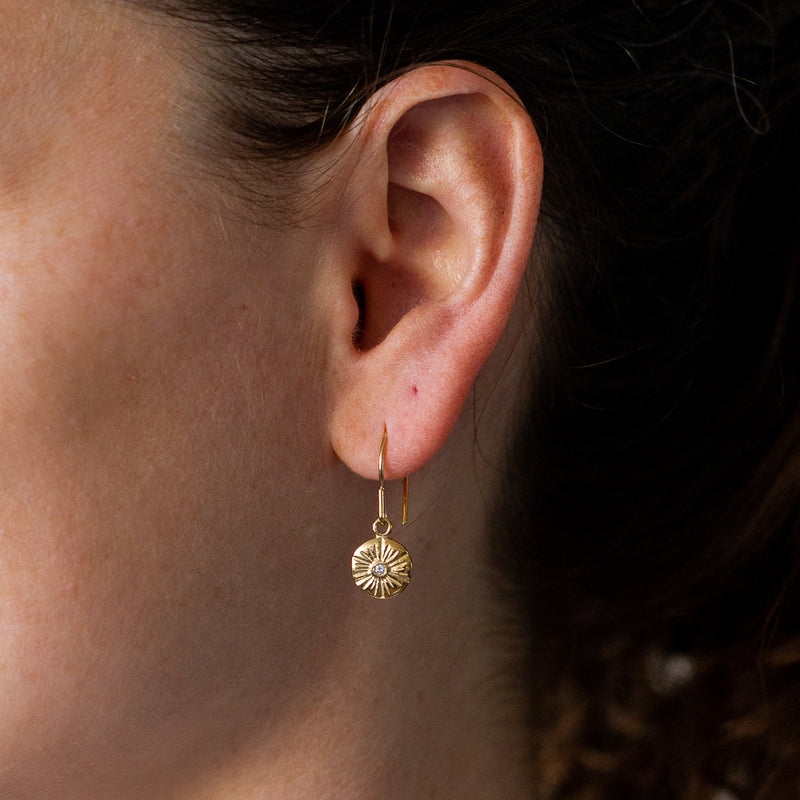 Medium round sunburst dangle earrings with a diamond center in gold vermeil hanging on an earby Corey Egan
