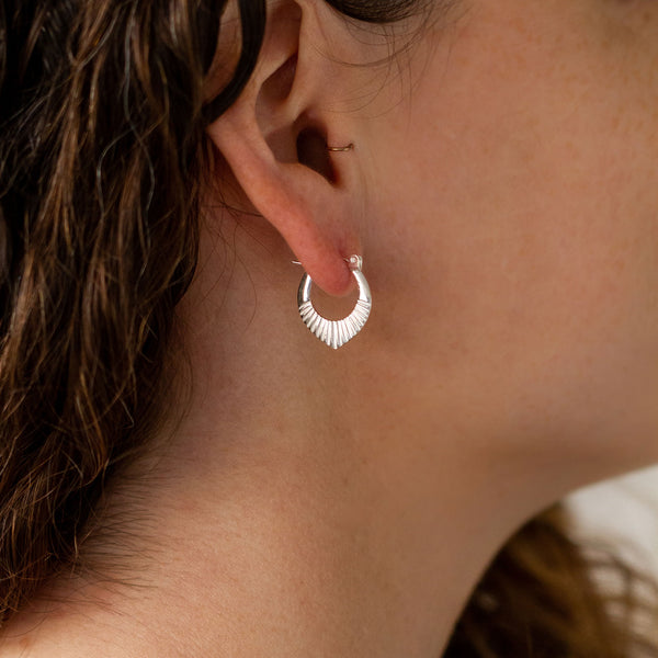 Silver Small Oblong hoops with hinge closure and sunburst bottom by Corey Egan