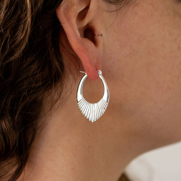 Medium Silver Oblong hoops with hinge closure and sunburst bottom by Corey Egan