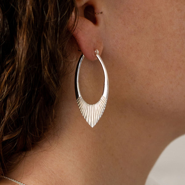 Large Silver Oblong hoops with hinge closure and sunburst bottom by Corey Egan