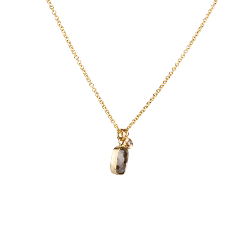A pendant of a cushion shaped rustic brown diamond in a gold bezel hangs on a gold chain next to a small engraved pendant with diamond center.