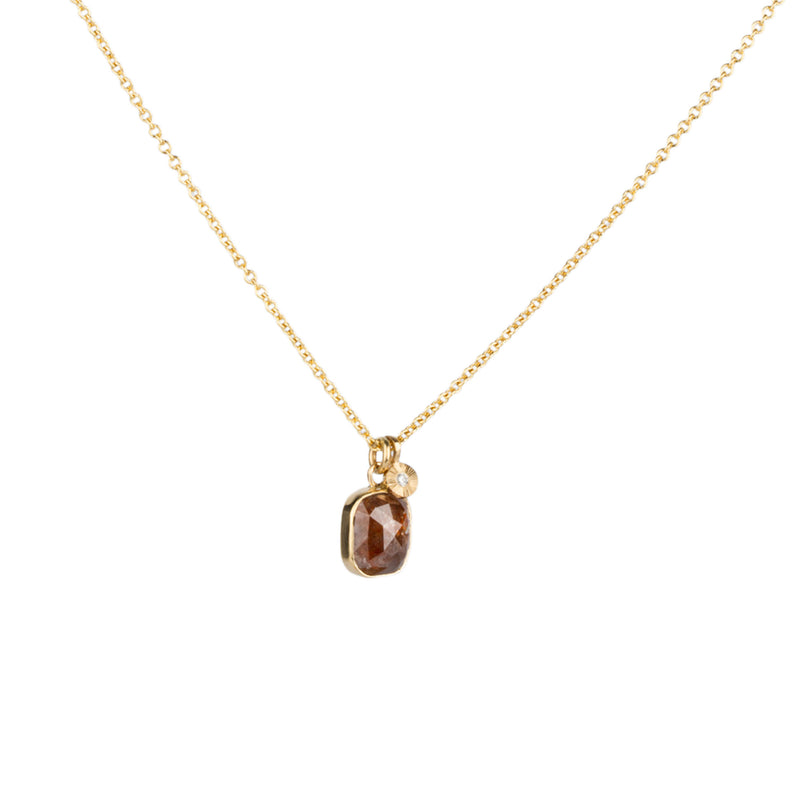 A pendant of a cushion-shaped rustic red diamond in a gold bezel hangs on a gold chain next to a small engraved pendant with a diamond center.