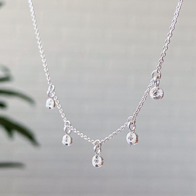 Silver and diamond station necklace with five tiny engraved pendants with diamond centers