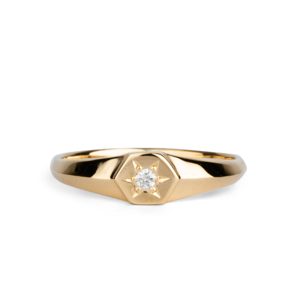 Low profile gold signet ring with hexagon top and a single white diamond set within a six pointed star setting