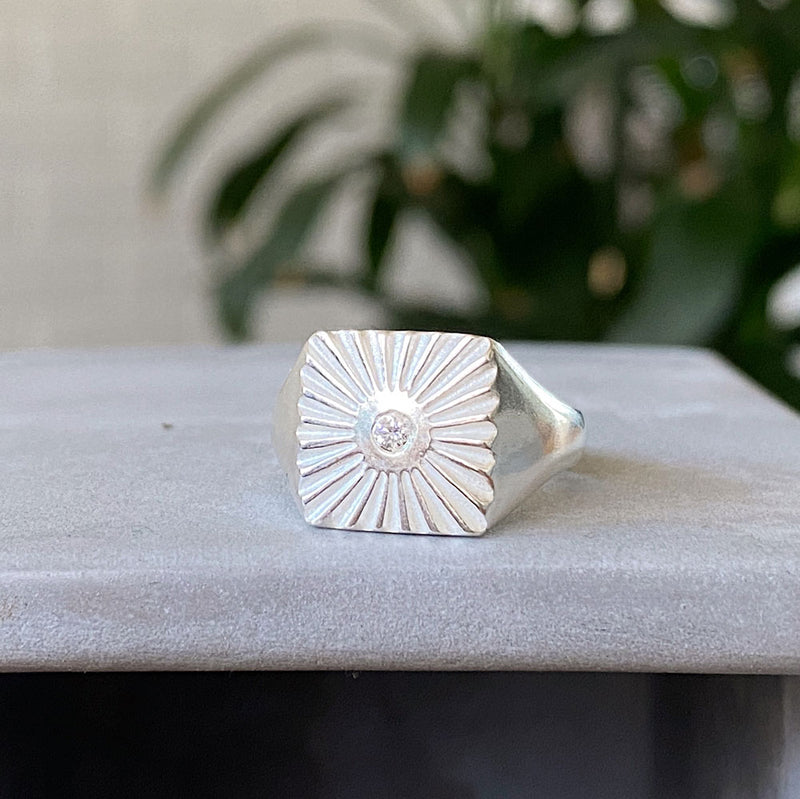 silver square sunburst signet ring with a diamond center