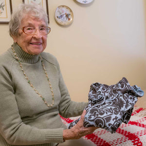 Pictured is Mary holding a set of comfortable fleece pajamas.
