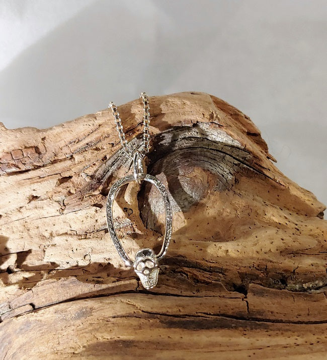 Skull pendant with freeform silver frame