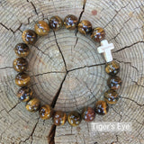 top view of the  Mens 'Thou Art With Me' Natural Stone Bead Cross Bracelets Tiger's Eye against the cut surface of a log