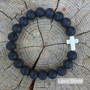 top view of the  Mens 'Thou Art With Me' Natural Stone Bead Cross Bracelets Lava Stone against the cut surface of a log
