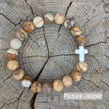 top view of the  Mens 'Thou Art With Me' Natural Stone Bead Cross Bracelets Picture Jasper against the cut surface of a log