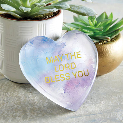 Photo of the May God Bless you paperweight on a table with decor around it.
