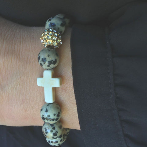 Close-up the 'Thou Art With Me' Dalmatian Stone with Ivory Cross Bead Bracelet worn on wrist
