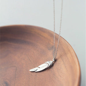 Photo of the Angel Feather Sterling Silver Necklace and wood bowl