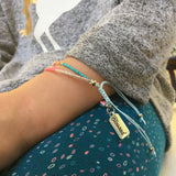 close up of a child's wrist wearing the multi-strand seed bead bracelet in pastel colors
