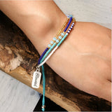 close up of a adults wrist wearing the multi-strand seed bead bracelet in turquoise colors