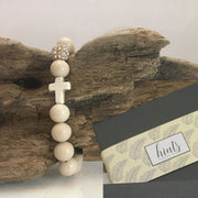 Close-up the 'Thou Art With Me' White Fossil Natural Stone  with Ivory Cross Bead  Bracelet over drift wood