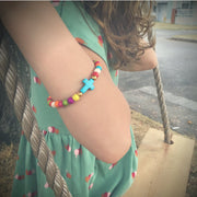 close-up photo of the Colorful ' jesus loves me' Youth bead bracelet with turquoise crosson young girls wrist