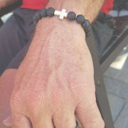 Close-up view of the  Mens 'Thou Art With Me' Natural Stone Bead Cross Bracelets Lava Stone on an arm