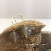 close-up of the  Natural Stone Blessing Earrings—Gray Agate bead and Sterling Silver Hook plated in 18k gold
