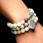very close-up of the Tree of Life Wrap Amazonite Bead Bracelet on Model's wrist with dark background