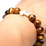 Close-up view of the  Mens 'Thou Art With Me' Natural Stone Bead Cross Bracelets Tiger Eye on an arm