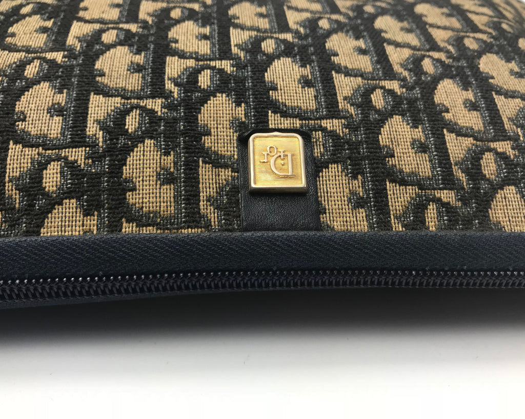 FRUIT Vintage Christian Dior 1980s navy trotter monogram clutch bag. Features a pochette style curved shape with top zipper and leather lining.