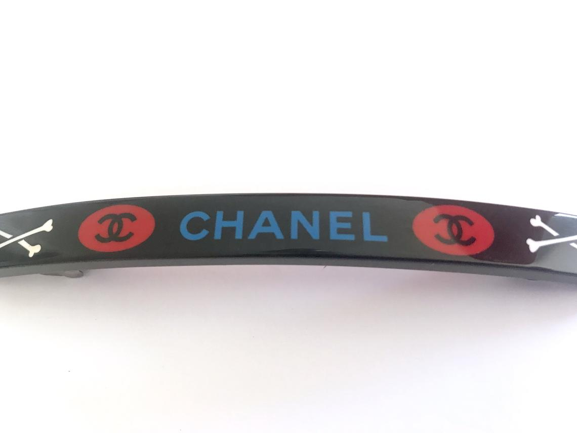 Fruit Vintage Chanel 2003 text logo barrette in black with cross bones. Features large Chanel text logos and two CC monograms either side.