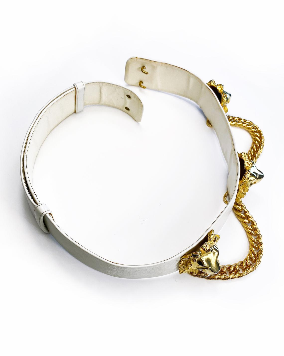 Fruit Vintage iconic Judith Leiber lions head belt with drop chains. This piece is amazing! It features 3 very large gold tone metal lions heads with drop chains on a white leather belt.