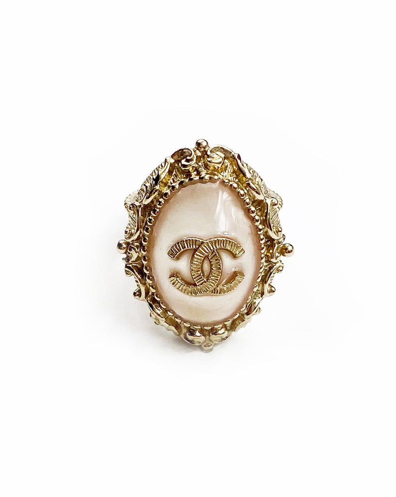 Fruit Vintage Chanel glass set logo ring. Features an ornate filigree style setting with pale pink glass stone with large CC logo inset.