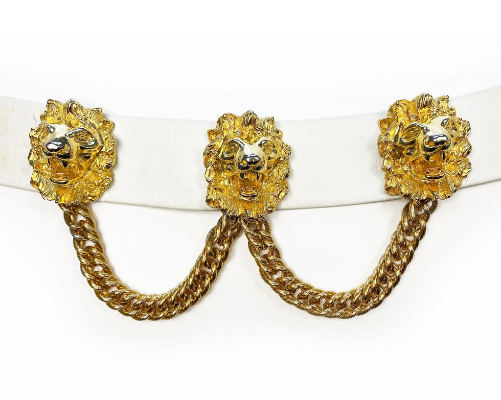 Fruit Vintage iconic Judith Leiber lion head belt with drop chains. This piece is amazing! It features 3 very large gold tone metal lions heads with drop chains on a white leather belt.