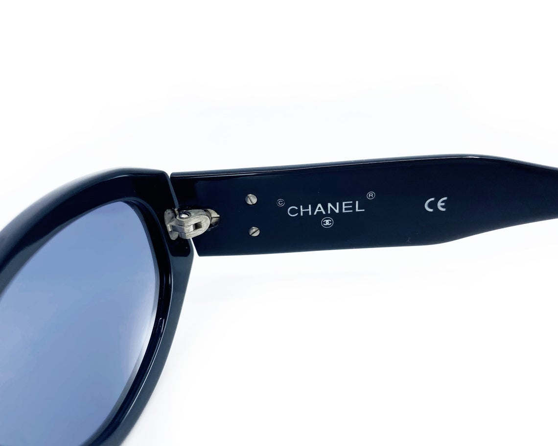 Fruit Vintage Chanel 1990s studded logo sunglasses. They feature silver screw shaped studs to the front of the frame and Chanel CC logo monograms to each side.