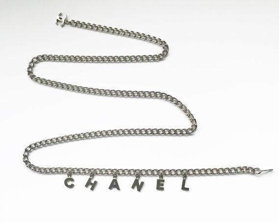 Fruit Vintage Chanel logo monogram letter chain belt in classic silver. Features a hook closure and logo drop Chanel CC charm.