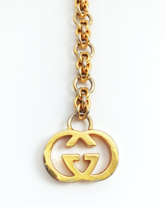 Fruit Vintage 1980s Gucci logo chain belt in classic gold. Features a lobster clip closure and significant logo drop Gucci GG charm.