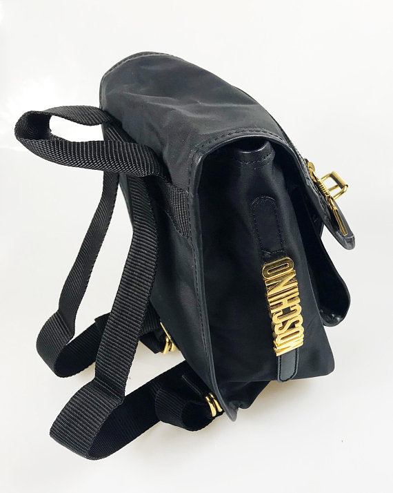 FRUIT Vintage Moschino mini backpack bag with the iconic Moschino gold lettering logo to one side, classic Moschino M logo zipper pull, and Redwall logo lining.