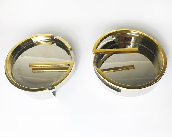 Fruit Vintage rare 1980's Gucci Logo double G ashtray set comprised of two interlocking gold and silver metal G-Shaped trays. This is the most amazing vintage designer home piece!