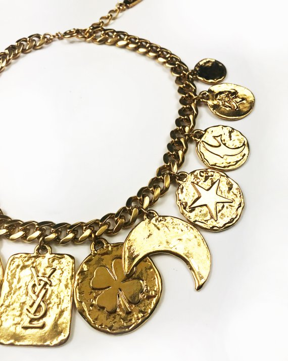 Fruit Vintage rare 1980s Yves Saint Laurent 'lucky charm' medallion necklace with textured logo. It features heavy gold plating in a deep yellow tone and various iconic YSL symbols such as the moon, clover, heart and bird.