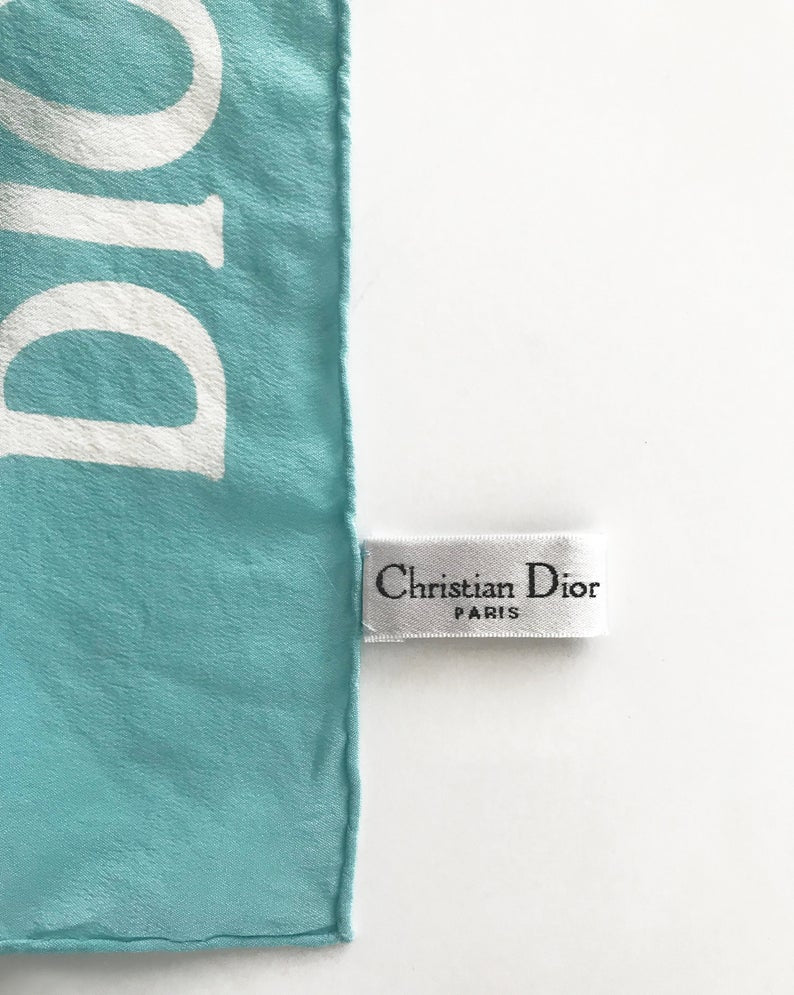 FRUIT vintage Christian Dior rare J'adore Dior logo monogram silk scarf perfect for use as a hair accessory, to tie around a hat or when worn around the neck. Features a bold graphic Dior logo print on both ends and hand finished rolled hem edging