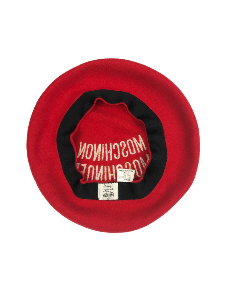 "FRUIT Vintage Moschino logo beret hat. It features large embroidered gold text with the slogal ""Moschinon Moschinoff"" and a classic beret hat shape."