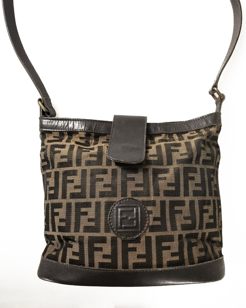 FRUIT Vintage Fendi Zucca cross body bucket bag dating to the 1980s. It features the classic Fendi Zucca monogram canvas, front embossed logo, top push button closure and long adjustable cross body strap.